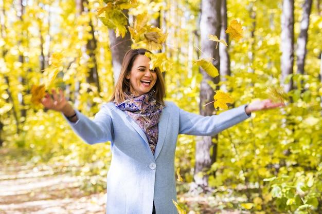 公園で紅葉で遊ぶ若い女性 Premium写真