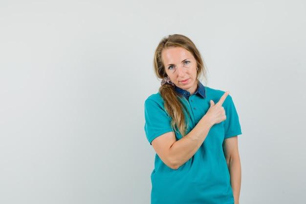 Giovane donna che punta lontano in t-shirt e guardando fiducioso Foto Gratuite