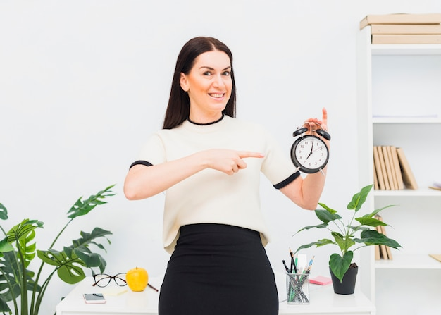 Young woman pointing finger at clock in office Free Photo
