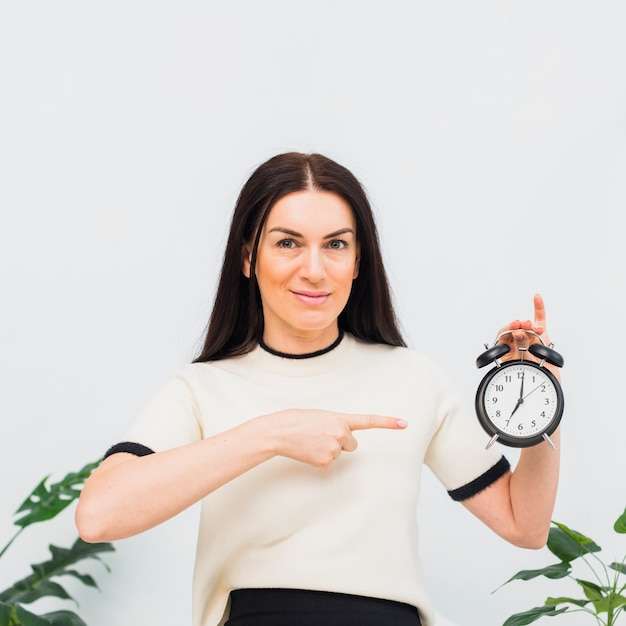 Young woman pointing finger at clock Free Photo