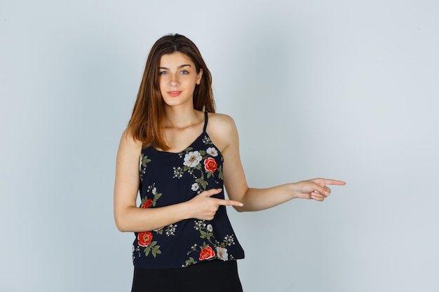 花のトップで横を指して、喜んでいる若い女性 無料写真