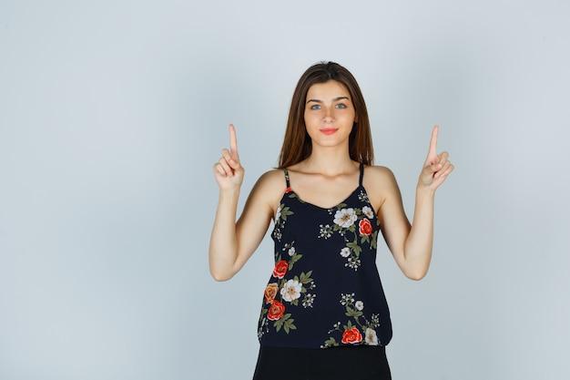 花のトップで上向きで自信を持って見える若い女性 無料写真
