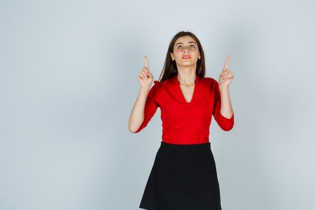 빨간 블라우스, 검은 치마에 검지 손가락으로 가리키는 젊은 여자가 집중 찾고 무료 사진
