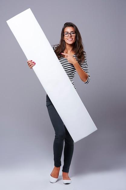 Giovane donna che punta sul tabellone per le affissioni bianco Foto Gratuite