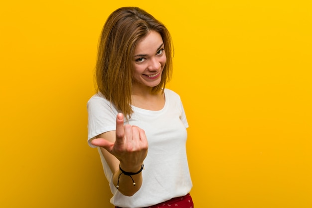 Young woman pointing with finger at you as if inviting come closer Premium Photo