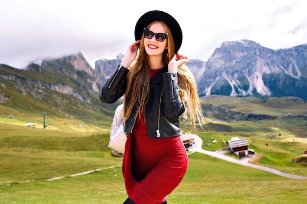 Giovane donna in posa alle montagne delle alpi, indossando abiti, giacca di pelle, occhiali da sole e zaino Foto Gratuite