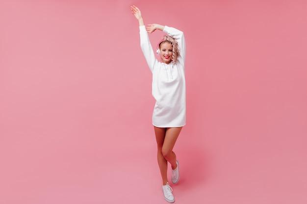 彼女のピンクのヘッドフォンでポーズをとって音楽を聴いている若い女性 無料写真