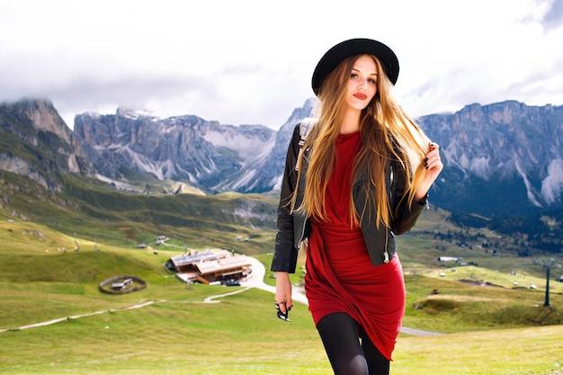 Молодая женщина позирует в альпах, в платье, кожаной куртке, солнцезащитных очках и рюкзаке Бесплатные Фотографии