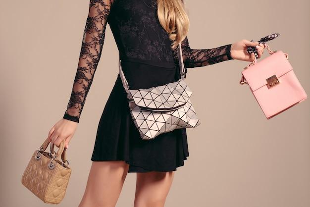 Młoda Kobieta Pozuje W Czarnej Sukni I Torebkach Premium Zdjęcia