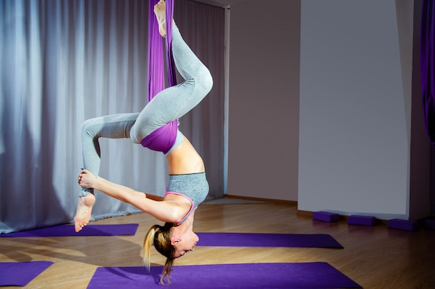 Young woman posing doing aerial yoga exercise with hammock upside down. Premium Photo
