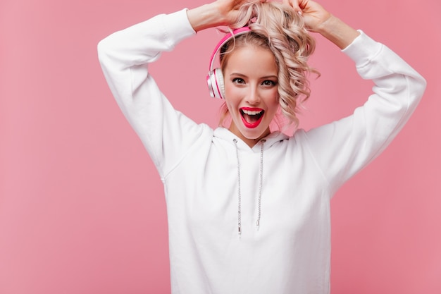 Young woman posing and listening to music through her pink headphones Free Photo