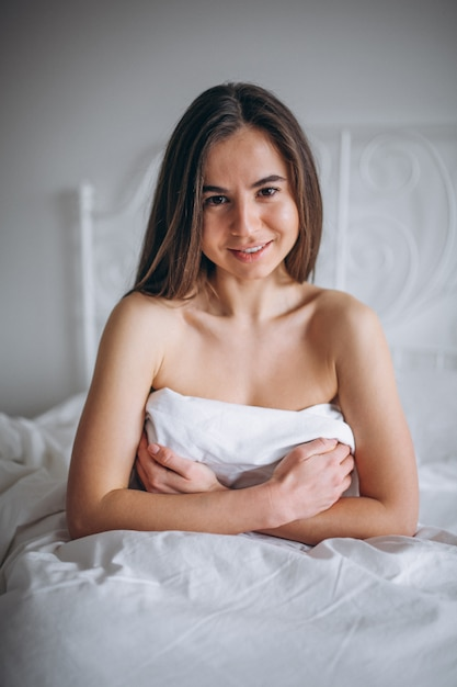 Young woman posing naked in bed Photo | Free Download