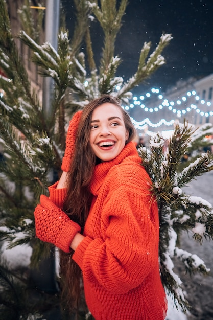 Young woman posing near the christmas tree on the street Free Photo