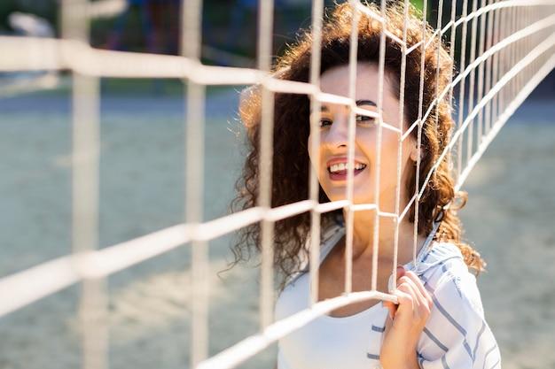 若い女性が外のバレーボールフィールドの横にポーズ 無料写真