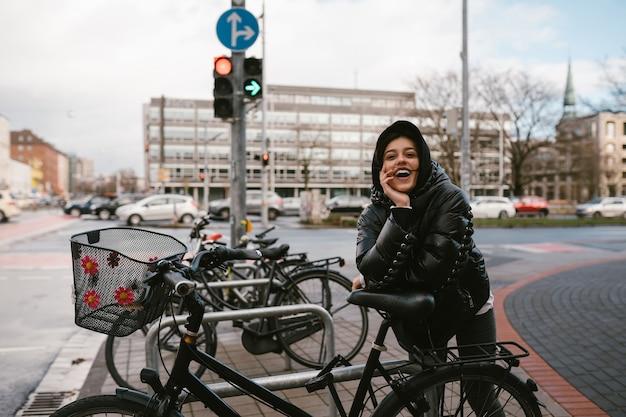 Giovane donna in posa in un parcheggio con le biciclette Foto Gratuite