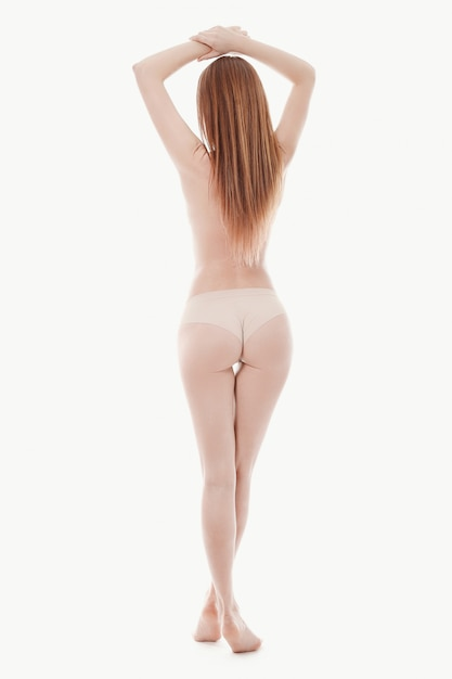 Young woman posing topless, perfect skin, back view Free Photo