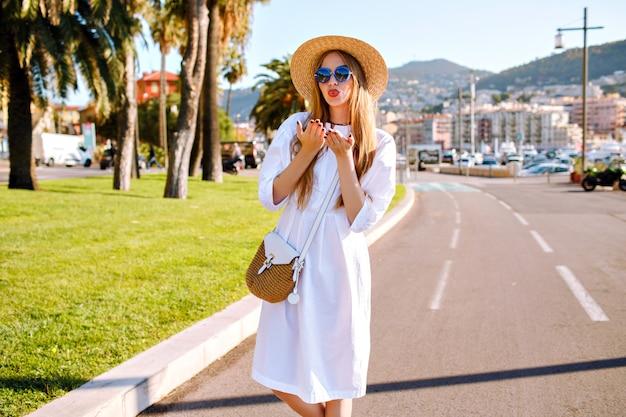 Giovane donna in posa e indossa un abito femminile elegante alla moda e accessori di paglia Foto Gratuite