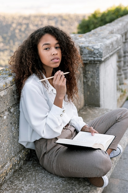 Young woman posing while holding a book Free Photo