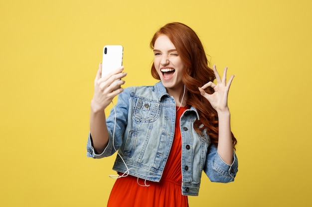 Young woman posing while photographing herself on smart phone camera for chat wit Premium Photo