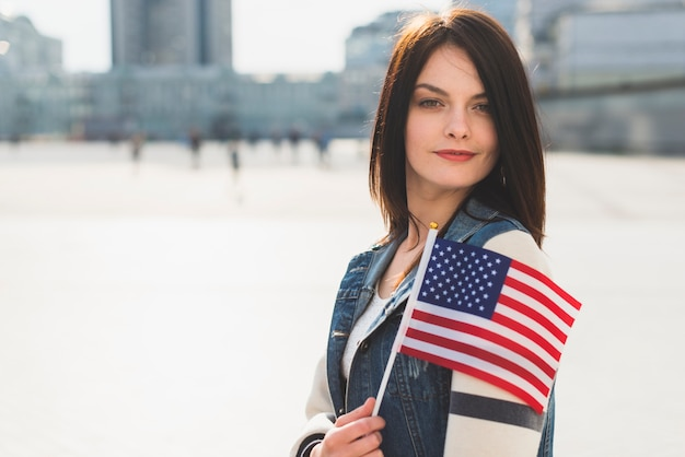 Young woman posing with american flag during fourth of july holiday Free Photo