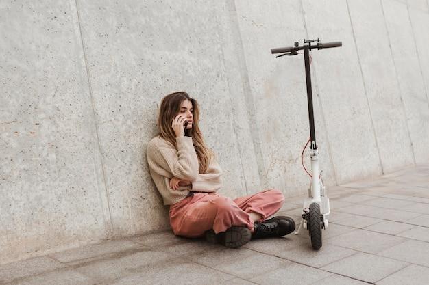 전기 스쿠터와 함께 포즈를 취하는 젊은 여자 무료 사진