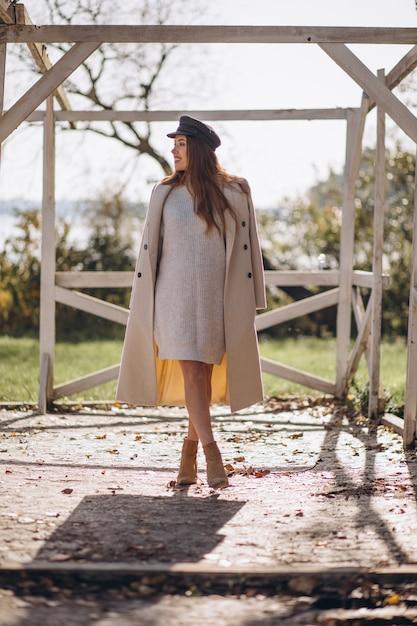 가 야외에서 패션 코트와 함께 포즈를 취하는 젊은 여자 무료 사진