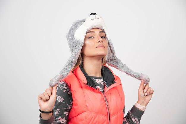 흰 벽에 재미있는 모자와 함께 포즈를 취하는 젊은 여자. 무료 사진