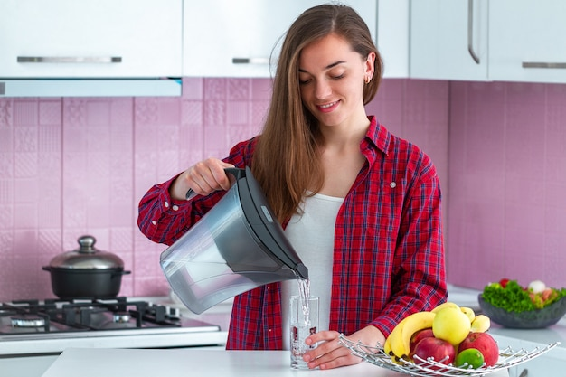 Young woman pouring fresh filtered water from water filter into a glass for drink at kitchen Premium Photo