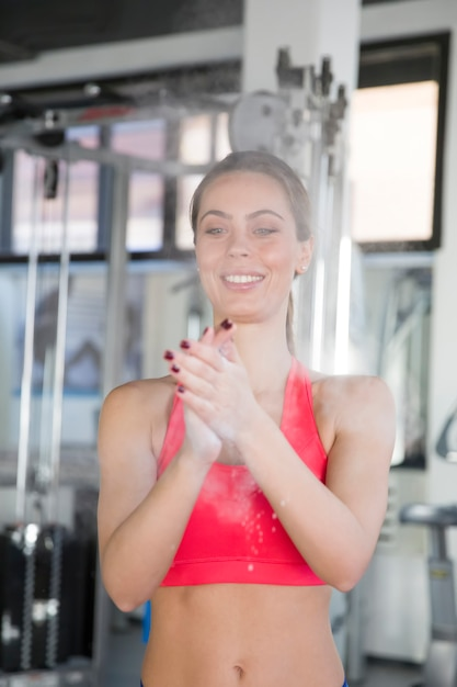 Young woman powder hands before exercise in the gym Premium Photo