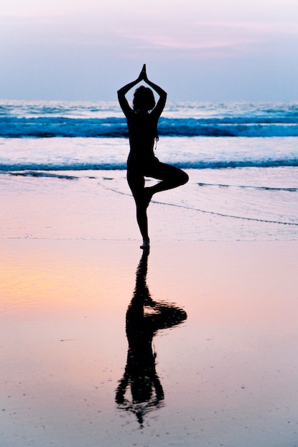 Young woman practicing yoga on beach in agonda, goa, india Premium Photo