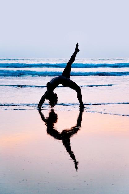 Young woman practicing yoga on beach in agonda, goa, india Premium Photo