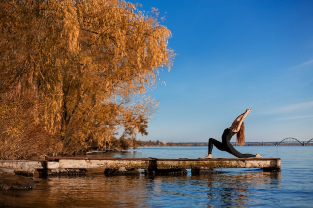 Young woman practicing yoga exercise at quiet wooden pier with city background. sport and recreation in city rush Premium Photo