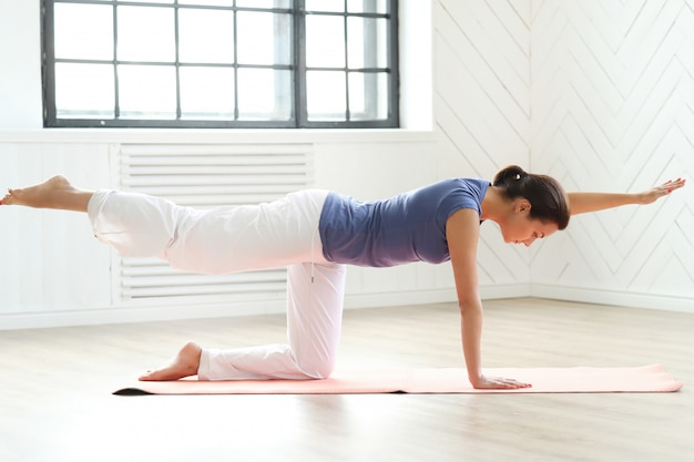Young woman practicing yoga on a yoga mat Free Photo