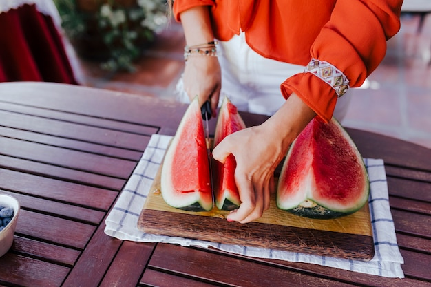 Young woman preparing a healthy recipe of diverse fruits, watermelon, orange and blackberries. using a mixer. homemade, indoors, healthy lifestyle Premium Photo