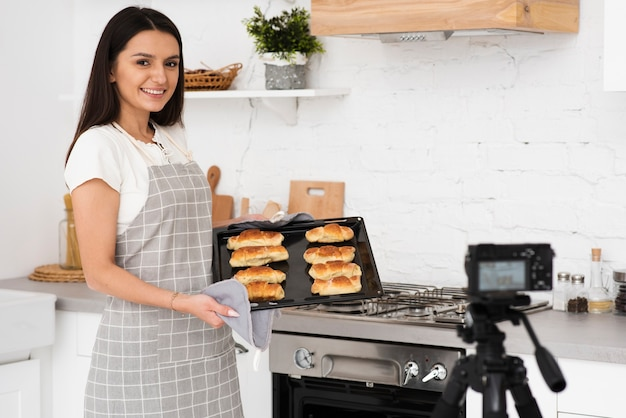 Young woman presenting pastries on camera Free Photo