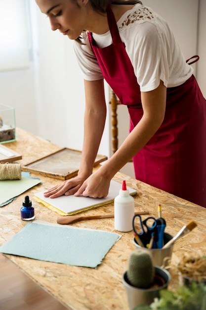 Young woman pressing paper pulp in mold Free Photo