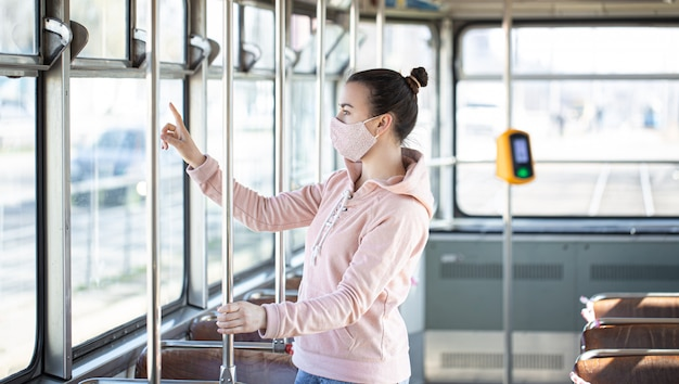 Young woman on public transport during the pandemic. Free Photo