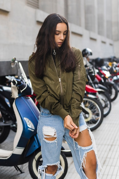 Young woman pulling the sleeves of jacket Free Photo
