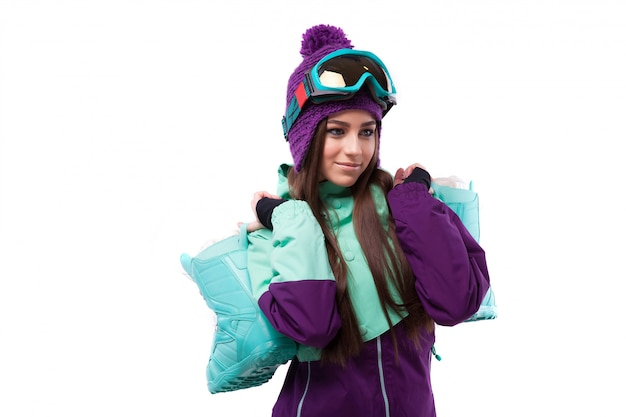 Young woman in purple ski outfit hold snow boots Premium Photo
