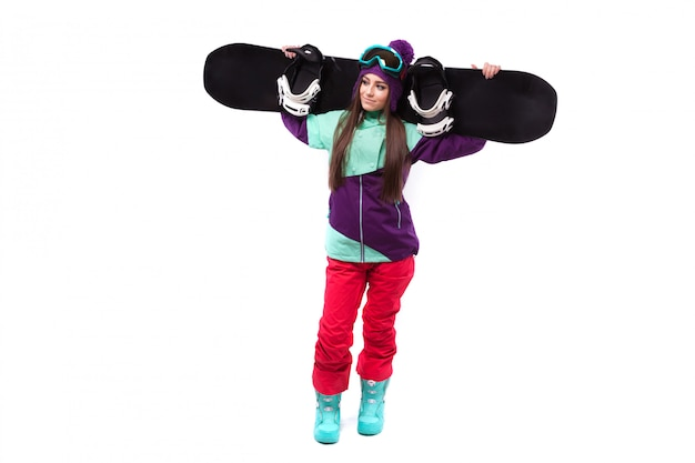 Young woman in purple ski outfit hold snowboard on sholders Premium Photo