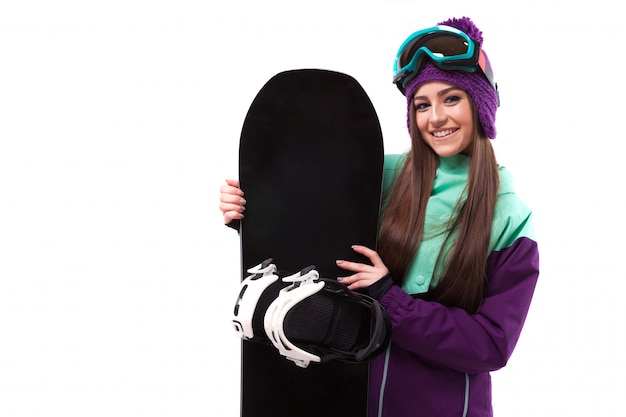 Young woman in purple ski outfit hold snowboard Premium Photo