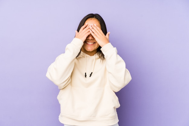 Young woman on a purple wall covers eyes with hands, smiles broadly waiting for a surprise. Premium Photo