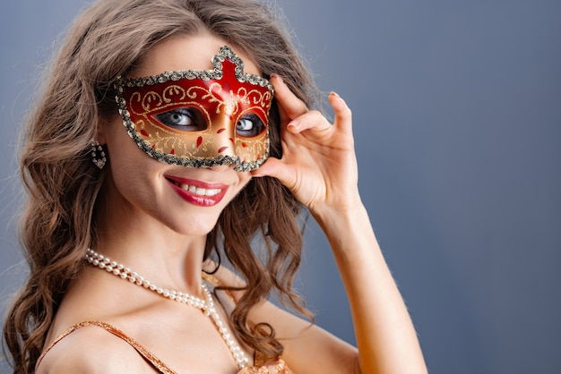 A young woman puts on a carnival mask Premium Photo