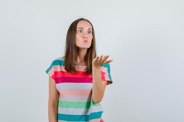 Молодая женщина агрессивно поднимает руку в футболке и выглядит сердитой, вид спереди. Бесплатные Фотографии