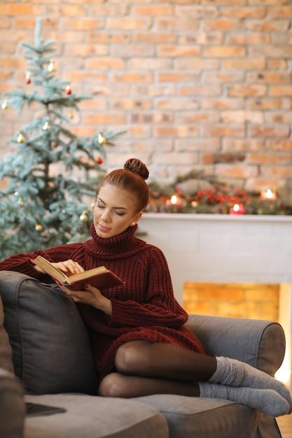 ソファで本を読んで若い女性 無料写真