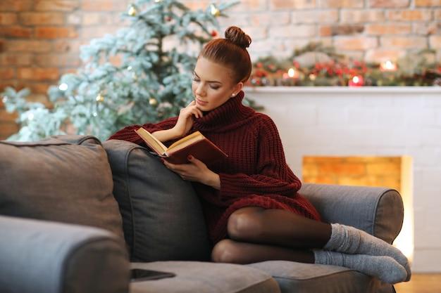 Молодая женщина читает книгу на диване Бесплатные Фотографии