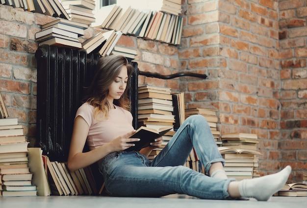 Giovane donna che legge un libro a casa Foto Gratuite