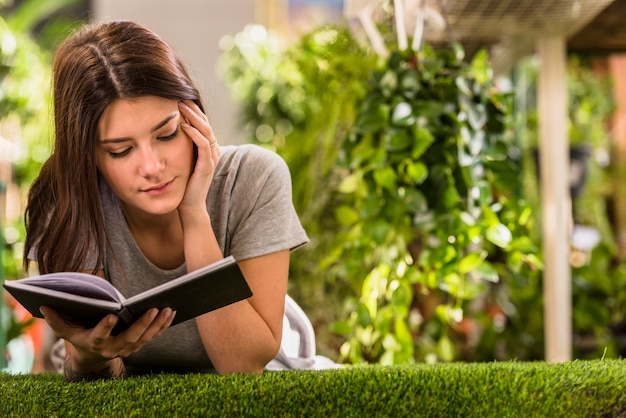 Young woman reading book and lying on lawn Free Photo