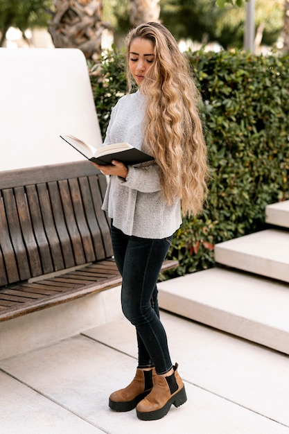 Young woman reading a book outdoors Free Photo