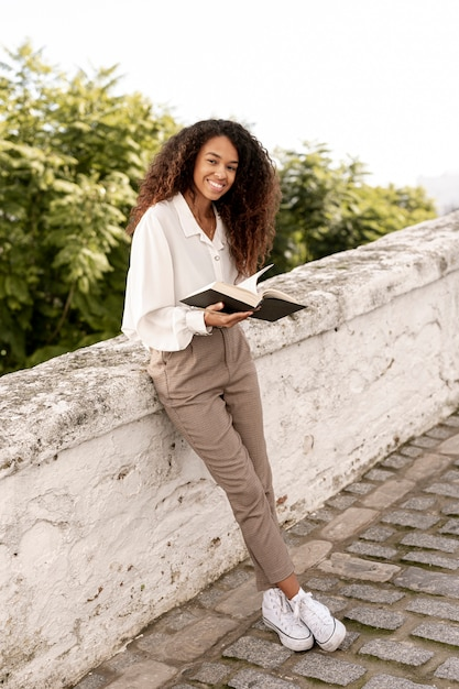 Young woman reading a book outside Free Photo